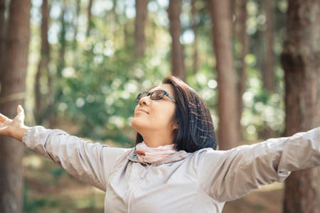 Closeup woman stretch the arms and breath the fresh air to feel relax in the forest Banco de Imagens