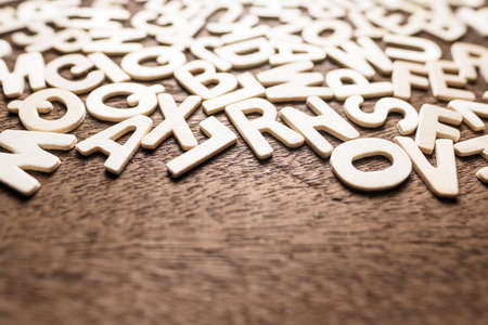 Closeup wooden English alphabets scattered on wood background, small letters equipment for English education