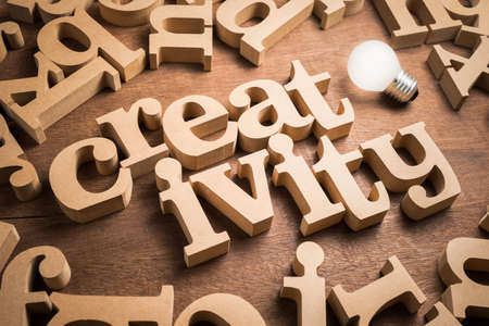 Creativity wood alphabets arranged in scattered letters on the table, creativity idea