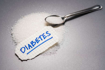 Diabetes handwriting text place on the pile of white sugar with teaspoon Banco de Imagens
