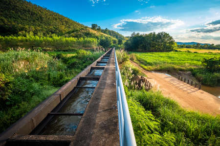 Water distribution bridge connected with irrigation canal to cross the lower land in the mountain, infrastructure in agriculture area, countryside of Thailand Banco de Imagens