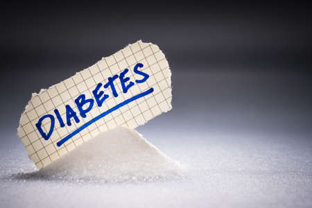 Diabetes handwriting text place on the pile of white sugar