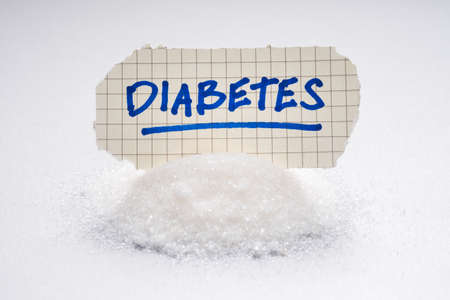 Diabetes handwriting text place on the pile of white sugar Foto de archivo - 135237521