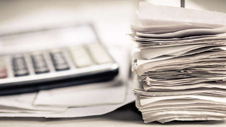 A lot of receipts in paper nail and calculator on the desk, accontancy or tax work concept