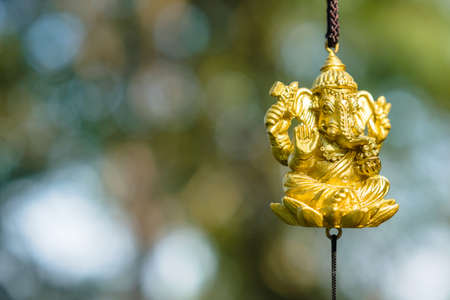 Golden Lord Ganesh small  figure hanged outdoor in the garden of temple area, Hindu religious god