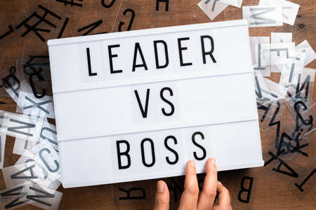 Hand insert the plastic alphabets into the sliding lightbox sign as Leader VS Boss concept