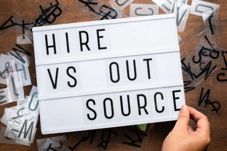 Hand insert the plastic alphabets into the sliding lightbox sign as Hire VS Outsource concept