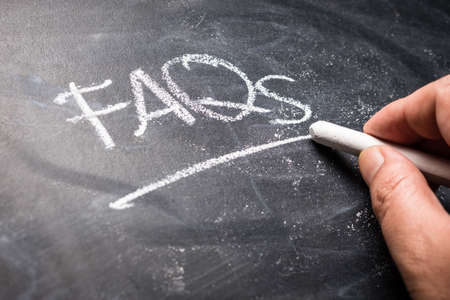 Closeup hand writing FAQs on blackboard, abbreviation of Frequently Asked Questions