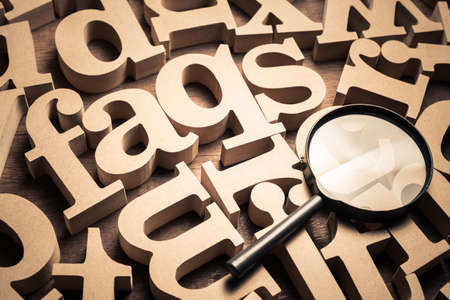 FAQs abbreviation (Frequently Asked Questions) in scattered English alphabets with magnifying glass