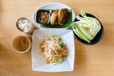 Som-Tam or sour and spicy papaya salad served with grilled chicken, sticky rice and fresh vegetables, tradional and popular combination of Thai food