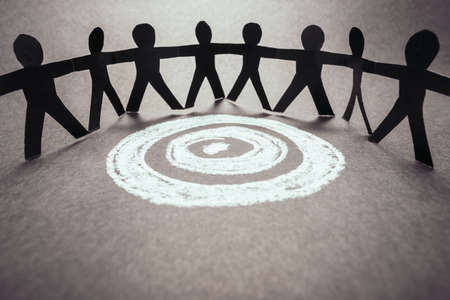 Paper human team stand around the target sketched by chalk, all for one mission, teamwork for success