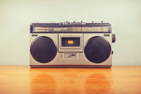 Retro portable radio with cassette player on wood table, outdated stereo boombox in vintage color