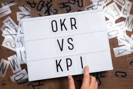 OKR versus KPI, hand insert the plastic letters into the sign light box, Objective Key Result and Key Performance Indicator