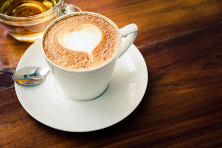New capuccino coffee with heart sign on top served in the white cup with hot tea on wood table