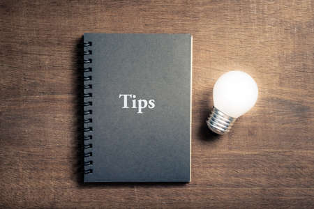 Black notebook with text TIPS and glowing light bulb on wood background Foto de archivo