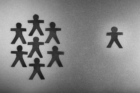 One paper human doll is separated from the group, symbolic for social distancing or other teamwork concept