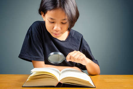 Child girl with magnifying glass over the pocket book, searching knowledge for education concept