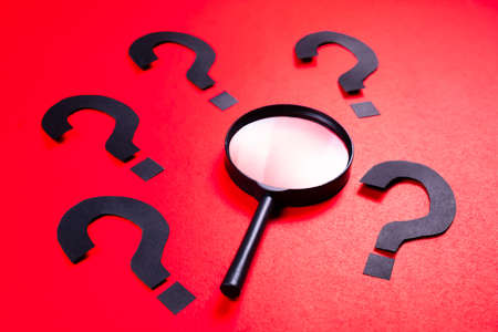 Magnifying glass with many question mark symbol on red paper