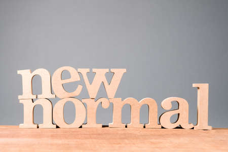 NEW NORMAL word by wood alphabets set on wood board and light green wall 免版税图像