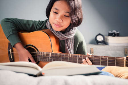 Closeup nine years old girl sitting on the mattress in her bedroom and practice guitar by looking the lyrics and chords in the lesson book in front of her 스톡 콘텐츠