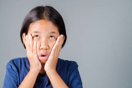 Nine years old girl do a funny weird face like she forget something or recall that she do something mistake