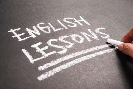 Closeup hand writing text : English Lessons on chalkboard Imagens