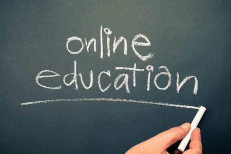 Closeup hand writing topic of ONLINE EDUCATION on chalkboard