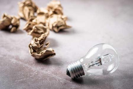 Closeup light bulb with crumpled trash paper balls, success and creative idea concept