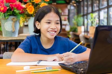 La niña disfruta y sonríe a la computadora portátil, la niña tailandesa aprende a educarse a sí misma mediante el contenido en línea