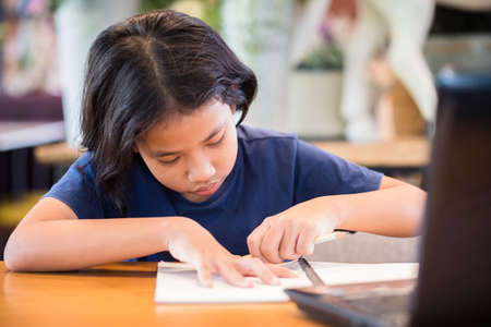 Child girl is erasing on notebook while learning online by computer laptop on the desk