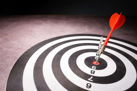 Closeup red dart hit accurate at the center of dartboard, business and goal setting concept
