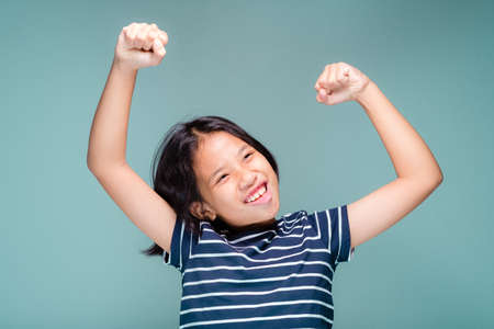 Ten years old girl clench her hand and lift the arms up with glad and satisfy to success, i can do it concept