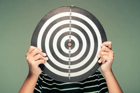 Child hold the dartboard in front of her face as goal setting concept Stock Photo