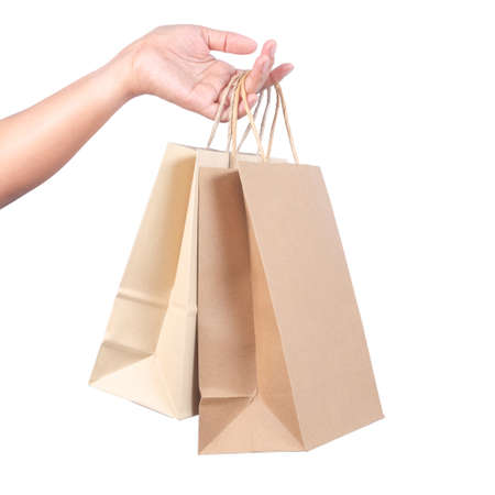 Woman's hand hold the shopping paper bags isolated on white background