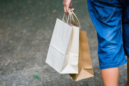 Closeup child holding the shopping paper bags and walk along the street