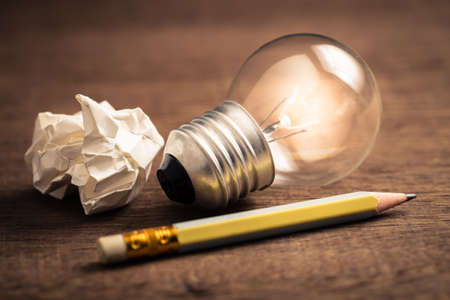 Pencil with glowing light bulb and crumpled paper on wood table, creative writing tips concept 写真素材