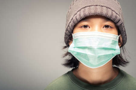 Closeup face of ten years old girl in knitting wool hat and wearing surgical face mask to prevent covid-19 virus pandemic