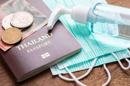 Closeup passport with hygienic face mask and alcohol spray bottle on the table, concept for travel in covid-19 global pandemic 写真素材