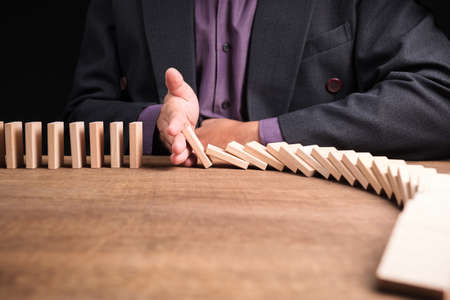 Businessman use his hand to stop the continuous falling domino on the table, business intervene and solving solution 写真素材