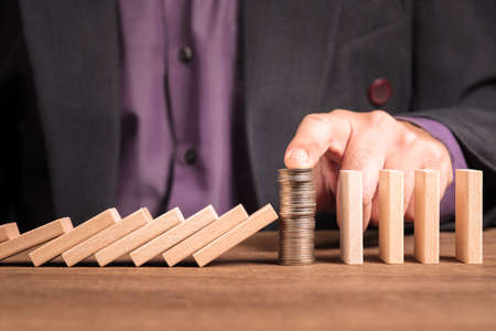 Businessman place the money heap in a row of wooden domino that continuously falling down to stop the crash
