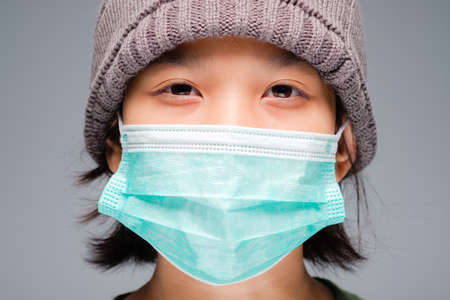 Closeup face of ten years old girl in knitting wool hat, wearing surgical face mask to prevent covid-19 virus pandemic 写真素材