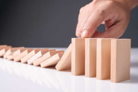 Closeup hand press on wooden block domino in a row to stop the falling of domino effect