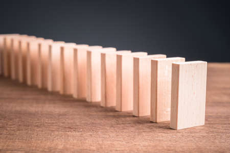 Wooden block domino standing stable on wood table, business chain and connection symbol, domino effect theory