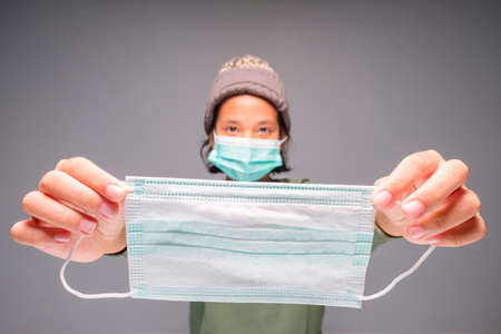 Child stretch out her hands with surgical mask from the back side to wear the mask to the others, prevention yourself from the virus concept