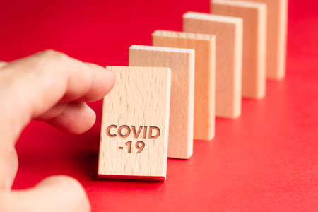Closeup hand push the first domino of Covid-19 and going to affect to the others fall down, consequences of Covid-19 pandemic 写真素材