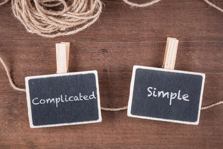 Small wood signs on clothespins clip on the rope with text : Complicated and Simple, for communication concept