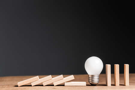 Small light bulb in a row of wooden domino, stop the falling domino, problem and solution or creativity concept