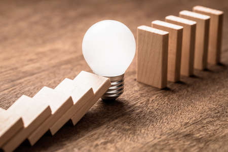 Glowing light bulb block the falling of domino in a row