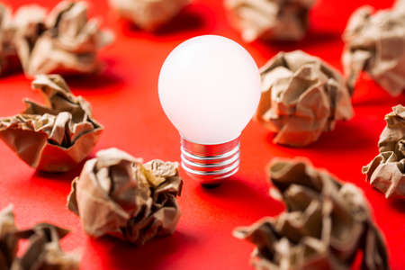 Small light bulb glowing among the crumpled paper balls
