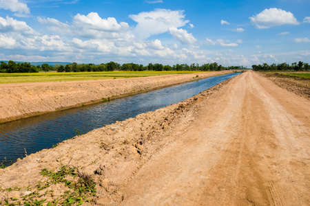 Dirt road and unfinished irrigation canal in the rice field, infrastructure during construction and development in countryside of Thailand